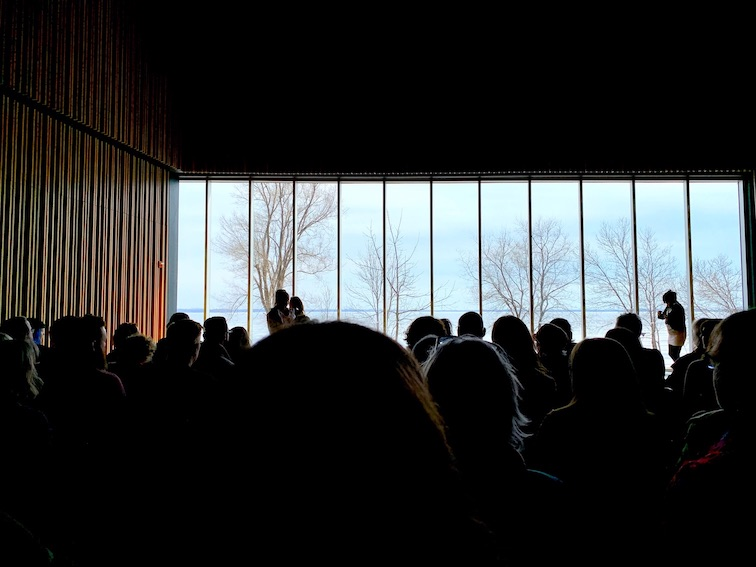 Image Caption: Audience watching Untitled by Tanya Lukin Linklater at Niigaani-Gichigami. Oniatarí:io, part of the Ka'tarohkwi Festival of Indigenous Arts at the Isabel Bader Centre for the Performing Arts.